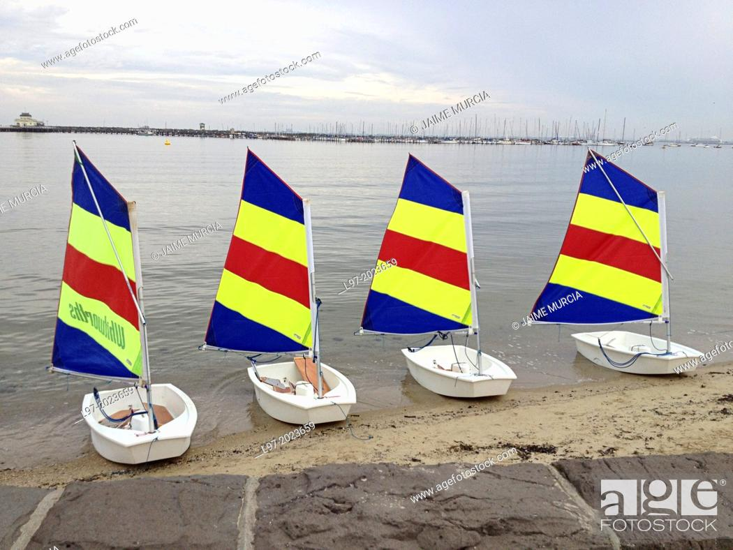 Stock Photo: Four small sail boats with multi coloured sails sitting on St Kilda beach, Melbourne Australia.
