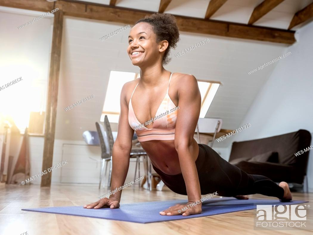 Stock Photo: Smiling young woman practicing yoga.