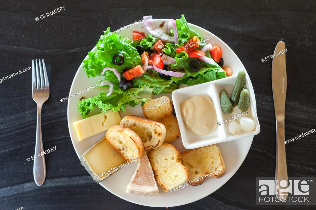 Stock Photo: A French chesse plate with Tomme, Belkot, and Saint Marcellin cheeses, salad, dijon mustard, pickles, and shallots.