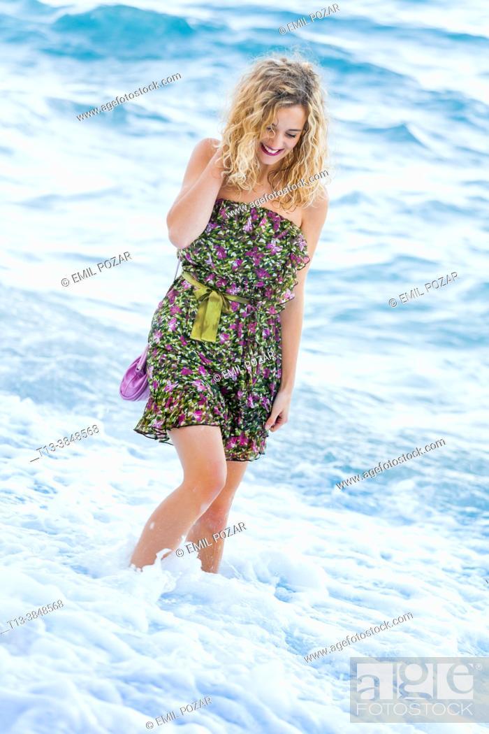 Imagen: Teen girl is playful watching down beach waves smiling happy.