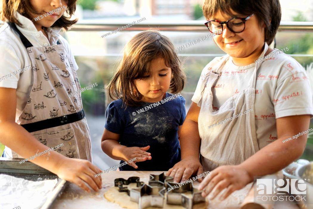 Stock Photo: Three children cutting out cookies.