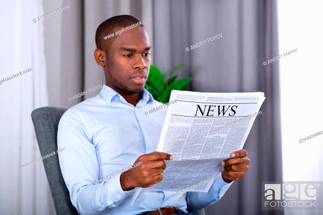 Stock Photo: Portrait Of A Young African Man Reading Newspaper.