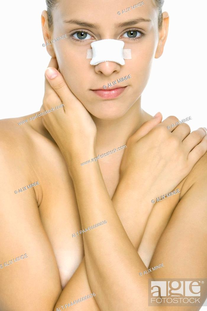 Stock Photo: Woman with bandaged nose, arms folded across chest, looking at camera.
