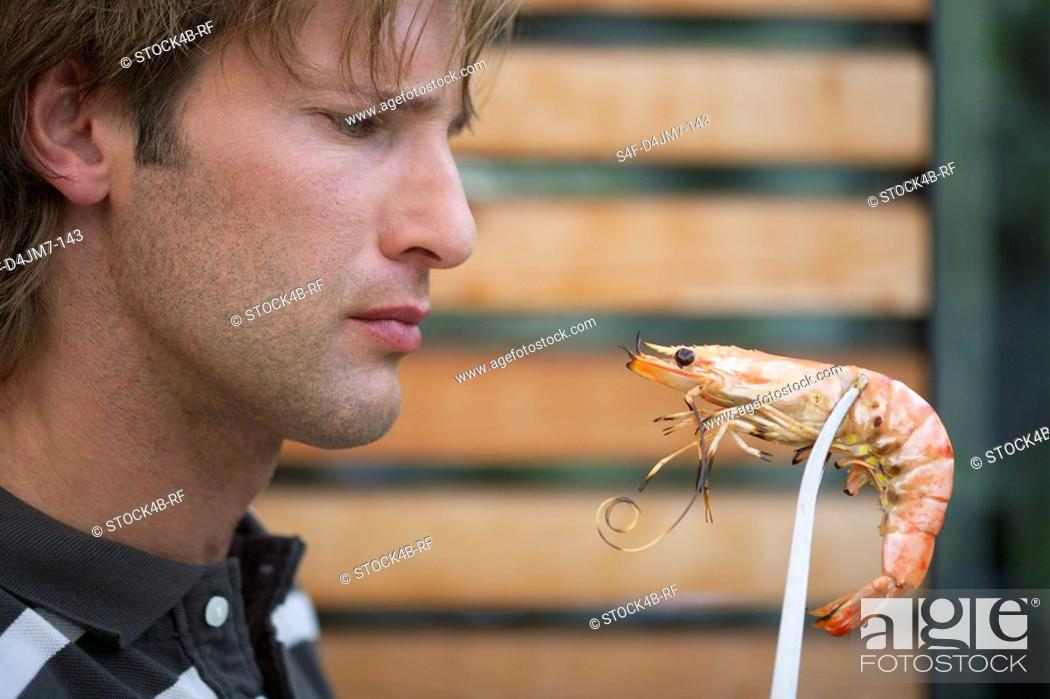 Stock Photo: Man holding a shrimp with gripper.