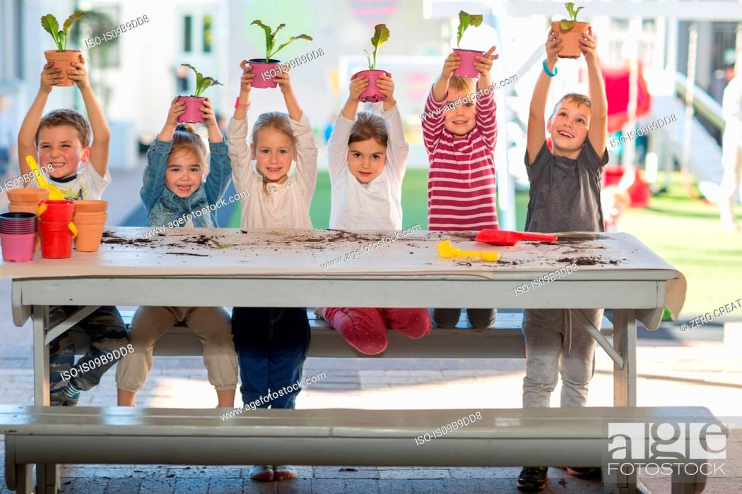 Stock Photo: Girls and boys at preschool, portrait holding up pot plants at picnic table.
