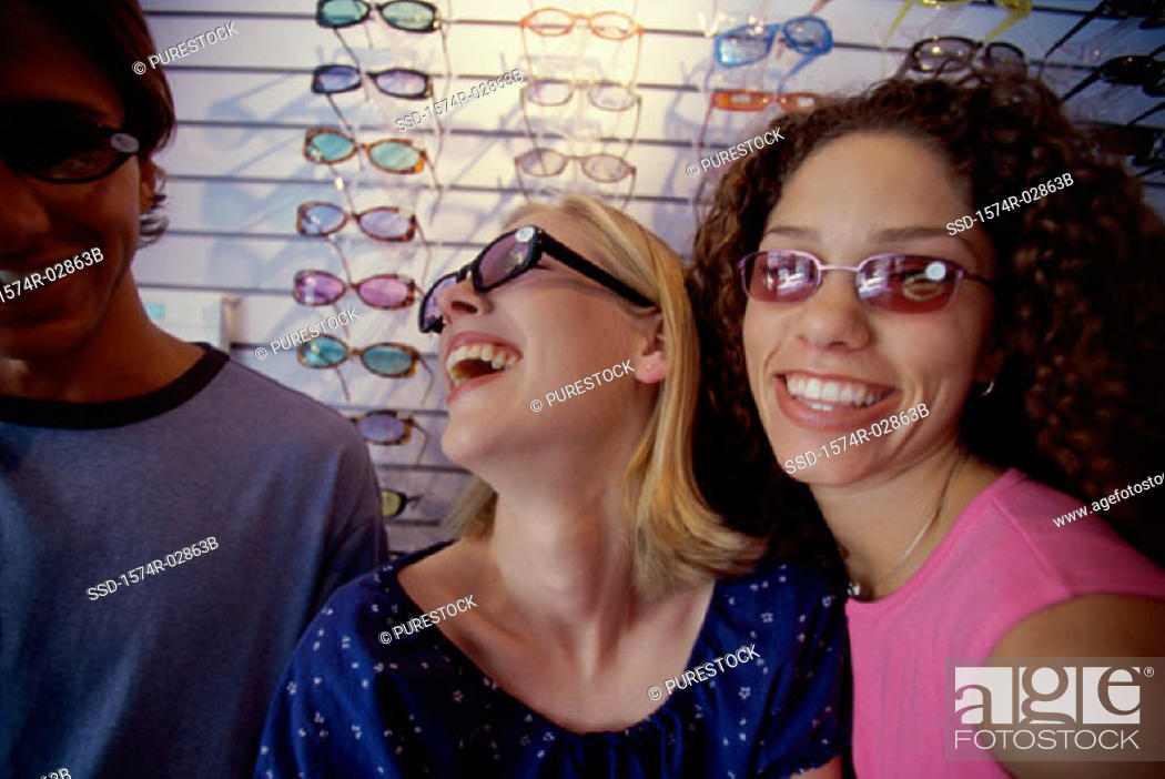 Stock Photo: Two young women and a young man wearing sunglasses in a store.