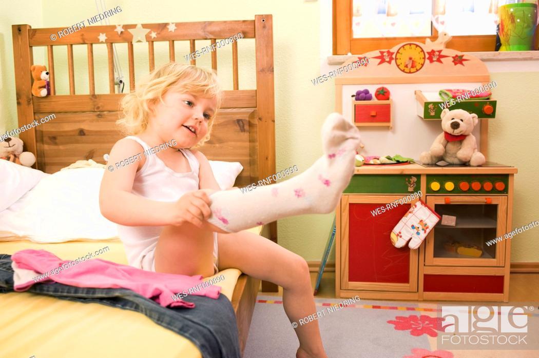 Stock Photo: Girl putting socks on bed.