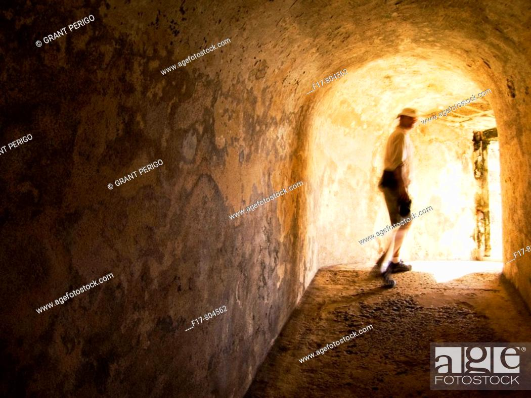 Stock Photo: a man walking into the light at the end of a tunnel.
