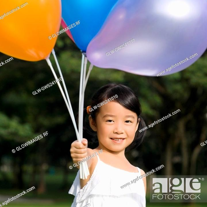 Stock Photo: Portrait of a girl holding balloons and smiling.