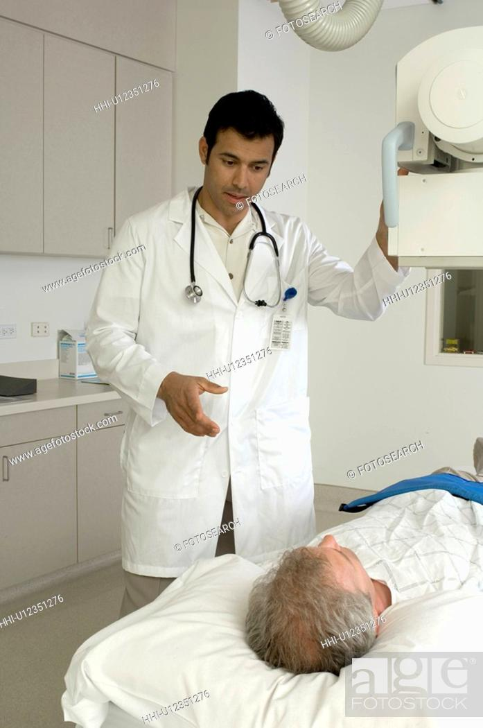 Stock Photo: Portrait of doctor treating older patient.