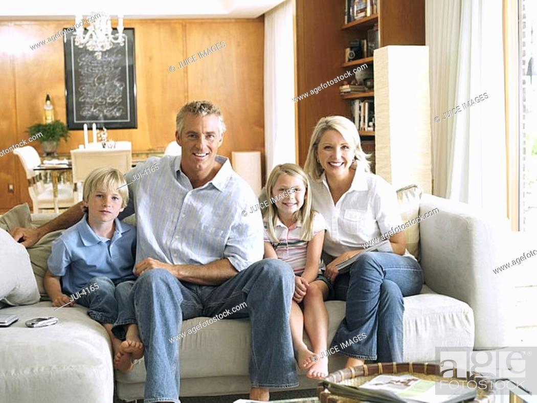 Stock Photo: Two generation family sitting on sofa at home, front view, portrait.