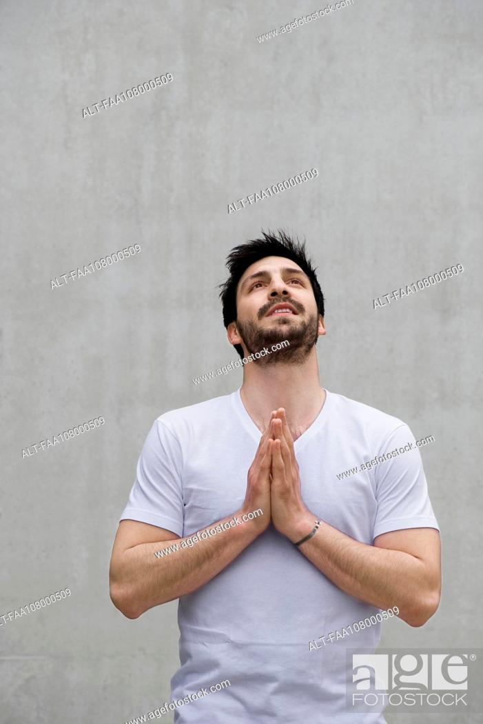 Stock Photo: Man with hands together, looking up.