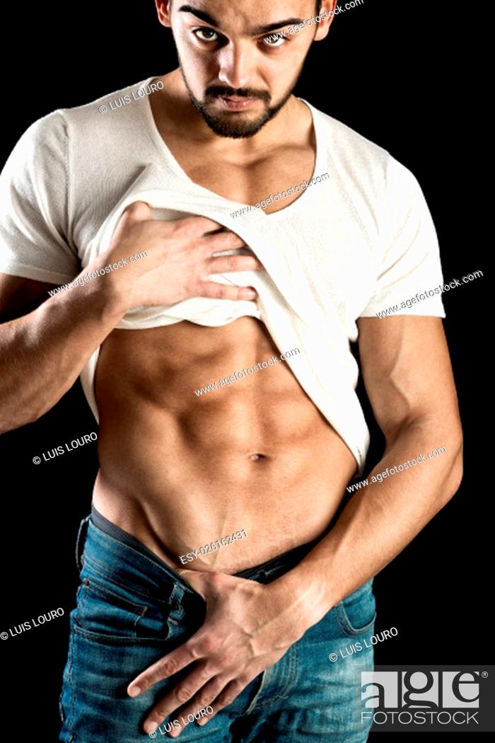 Stock Photo: Handsome and muscular young man showing his abdominals over a black background.