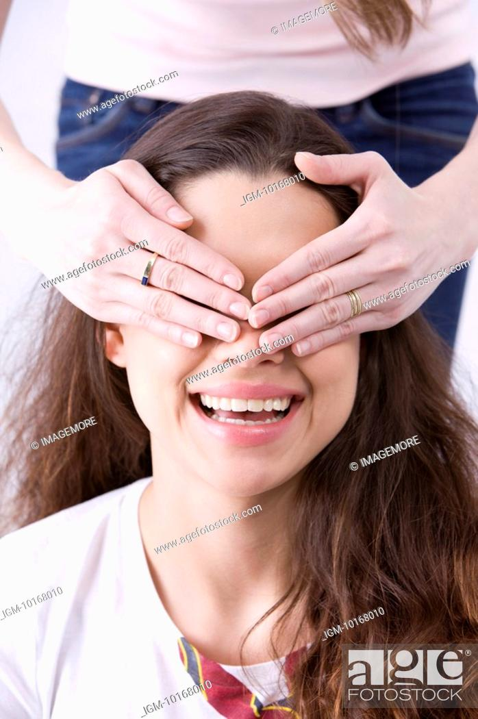 Stock Photo: Young woman covering eyes of friend.