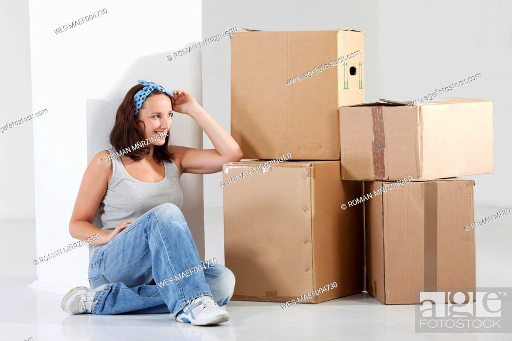 Stock Photo: Young woman sitting by cardboard box, smiling.