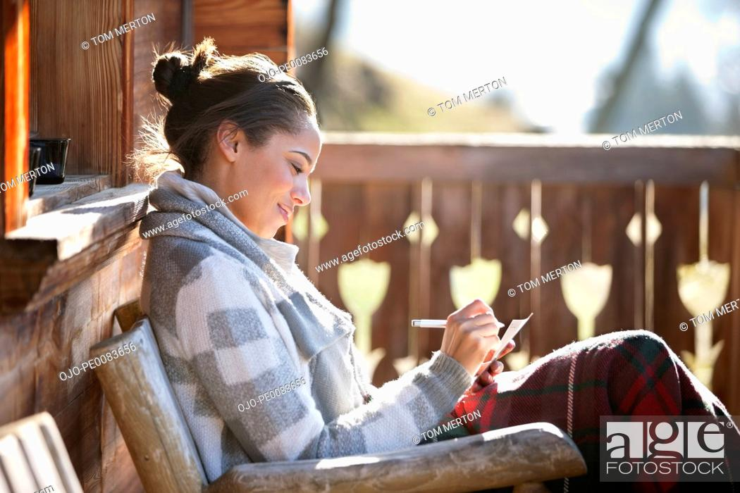 Stock Photo: Smiling woman with paper and pen on cabin porch.