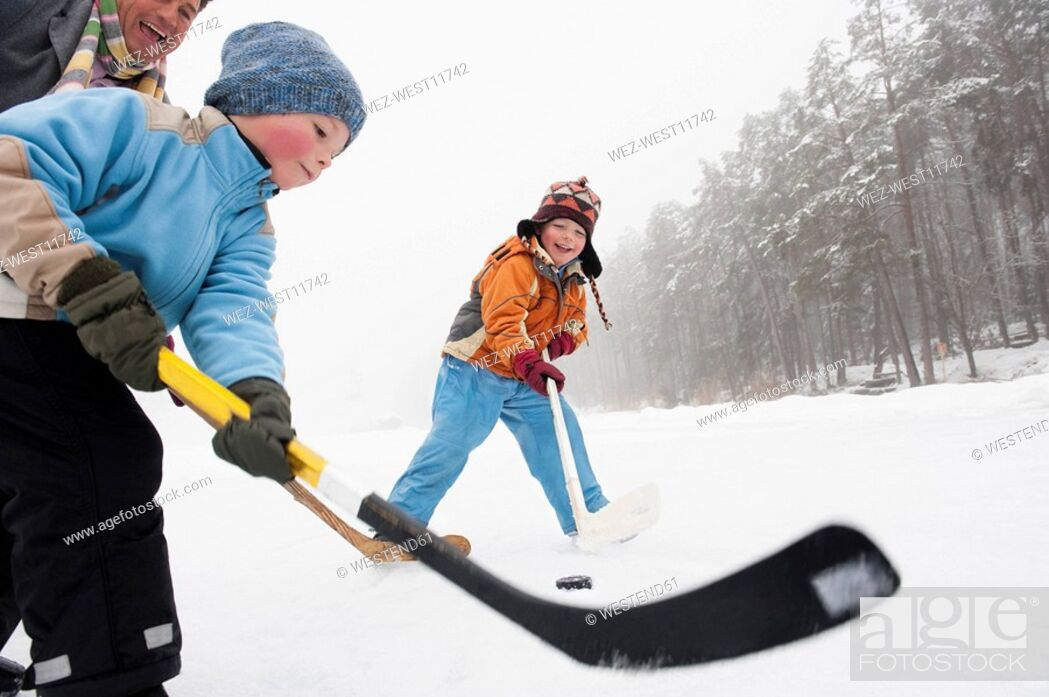 Stock Photo: Italy, South Tyrol, Seiseralm, Father and children 4-5 playing ice hockey.