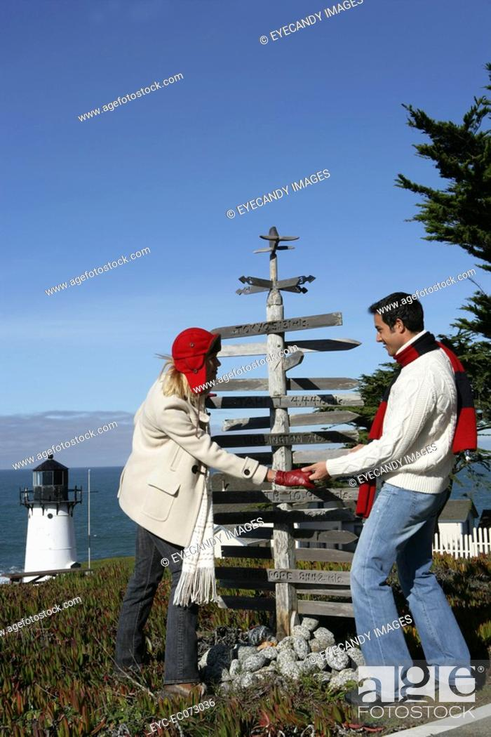 Stock Photo: Young couple looking at direction post at lighthouse.