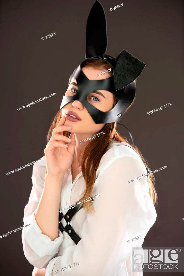 Stock Photo: Sexy young brunette wearing black leather bdsm bunny ears mask and white shirt shot against wall waist up portrait.