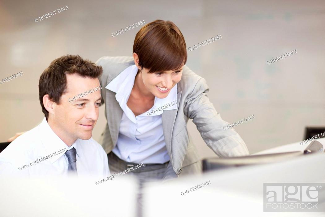 Stock Photo: Businessman and businesswoman using computer at desk.