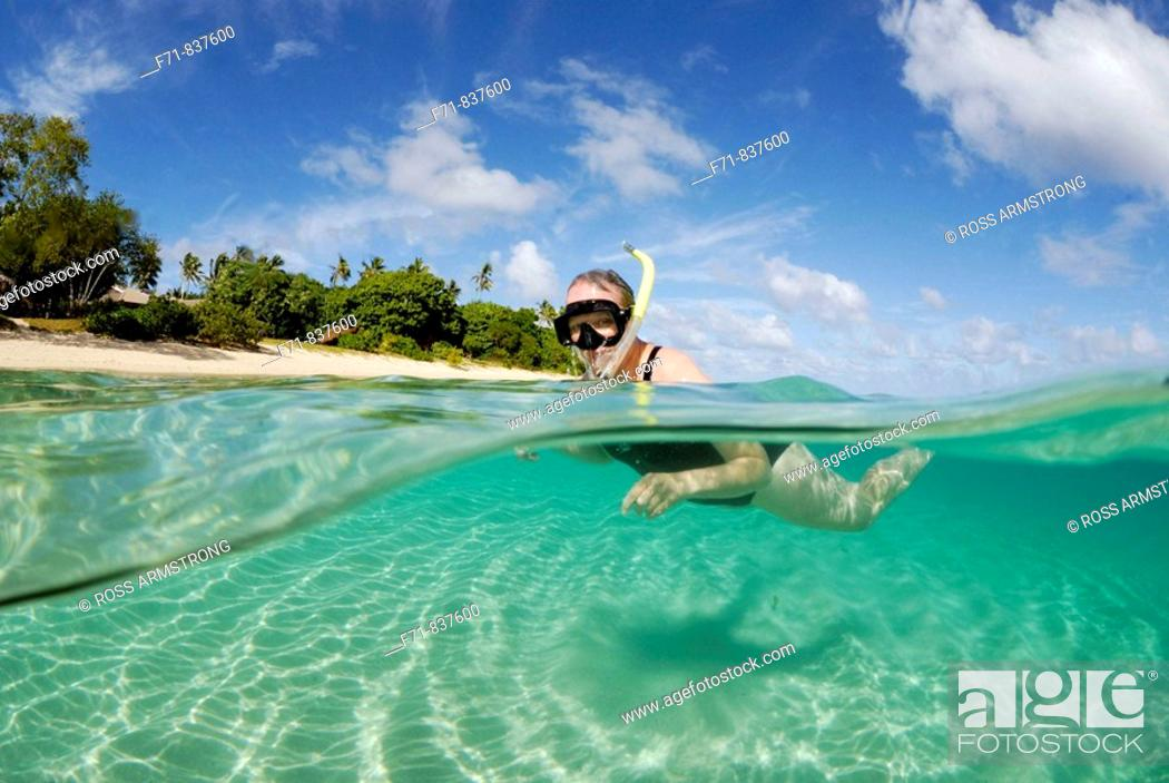 Stock Photo: Middle aged women in one piece swim suit snorkelling over sandy on tropical beach. Ha`apai Group, Tonga. South Pacific Ocean.