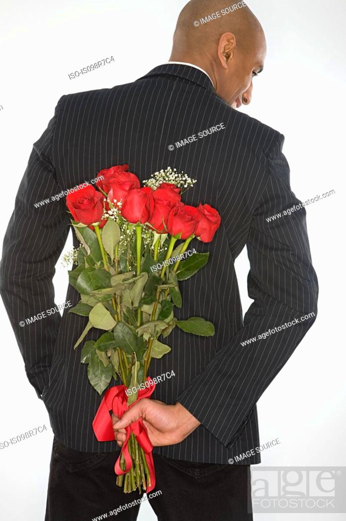 Stock Photo: Man with a bunch of roses behind his back.