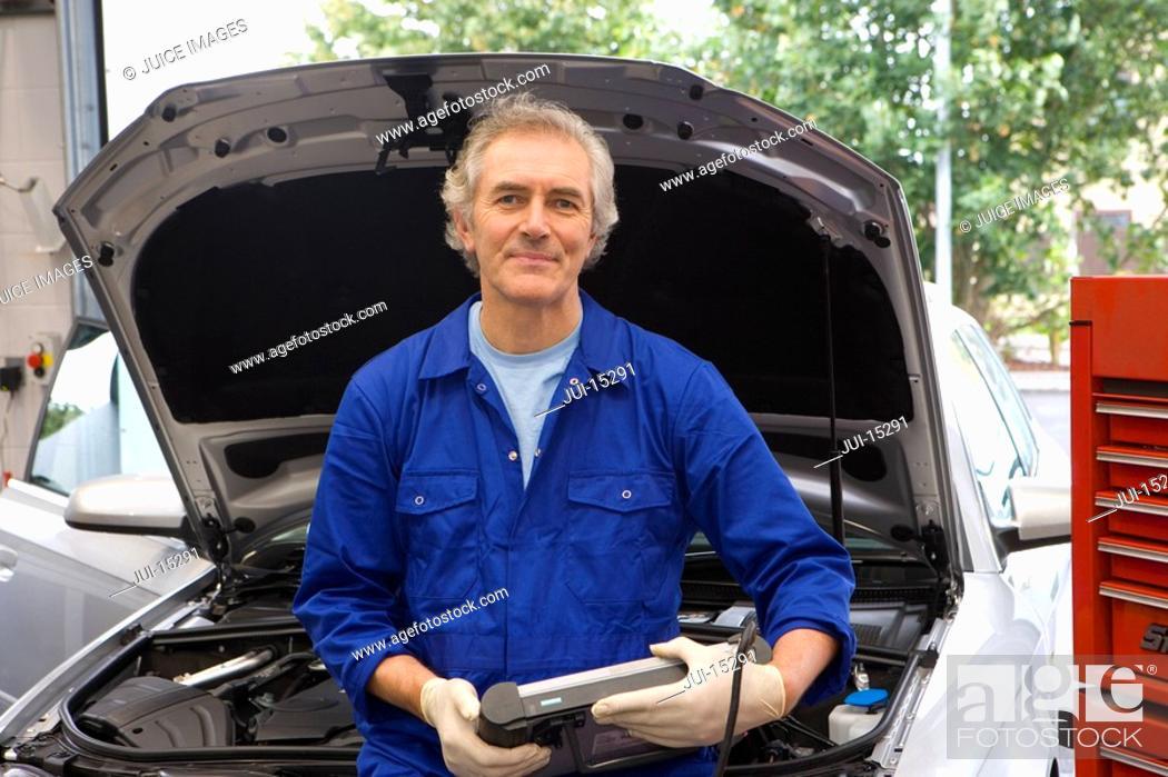 Stock Photo: Mechanic by open bonnet of car, portrait.