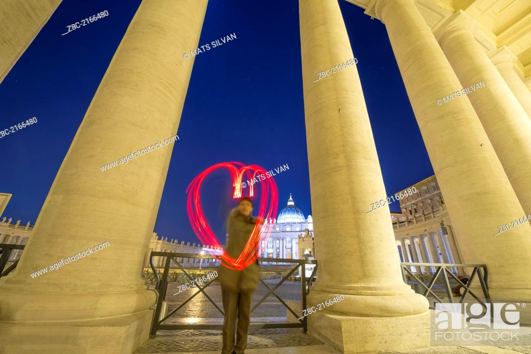 Stock Photo: Woman light painting a heart in Vatican City In Rome, Italy.