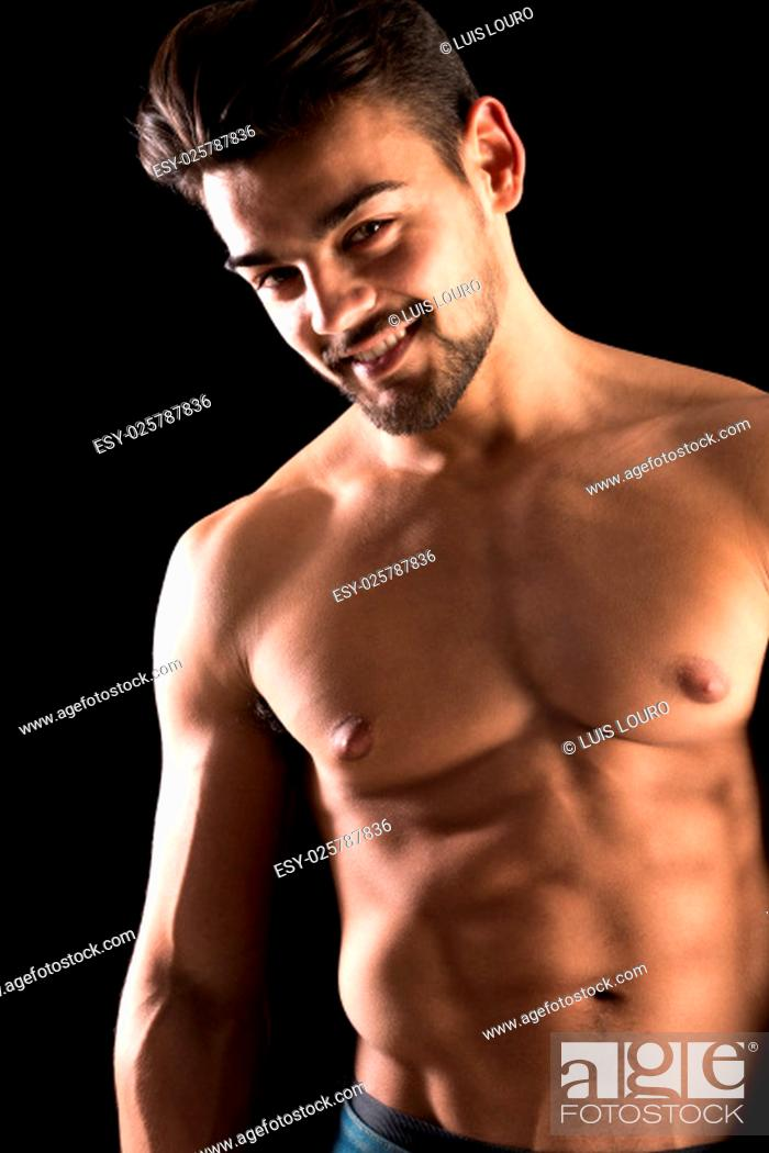 Stock Photo: Handsome young man, shirtless, with great body posing over a black background.