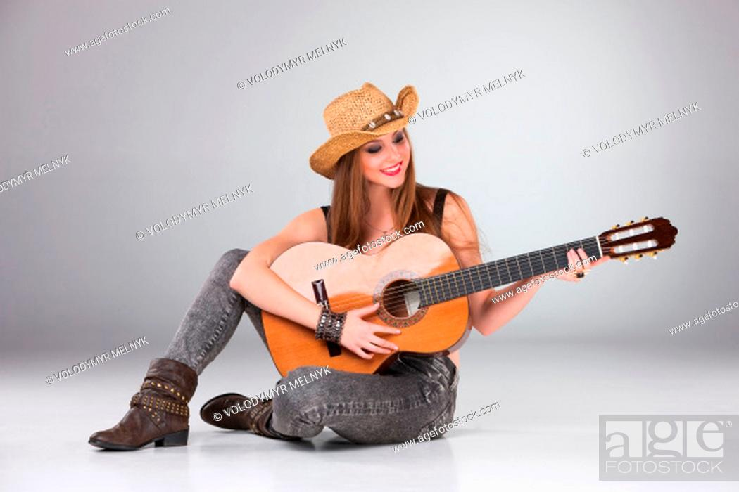 Stock Photo: The beautiful girl in a cowboy's hat playing acoustic guitar on a gray background.