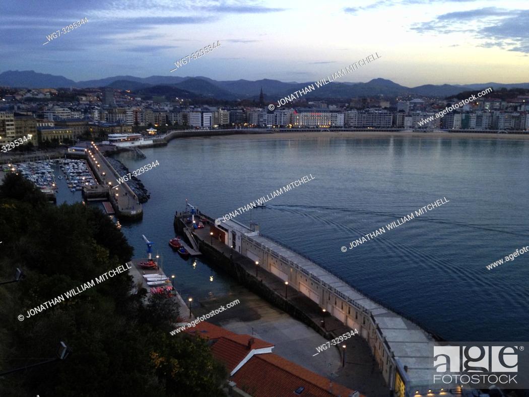 Stock Photo: SPAIN San Sebastian / Donostia -- 15 Nov 2014 -- A small inshore fishing boat returns to the harbour near the old quarter of San Sebastian / Donostia in the.