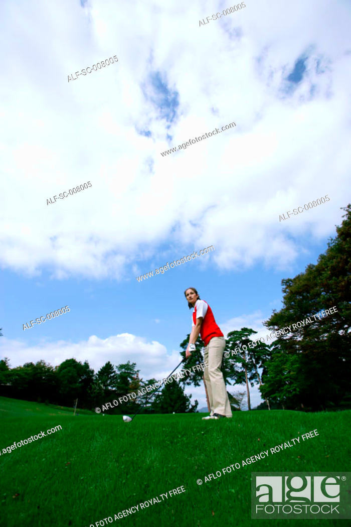 Stock Photo: Young woman contemplating before playing a golf shot.