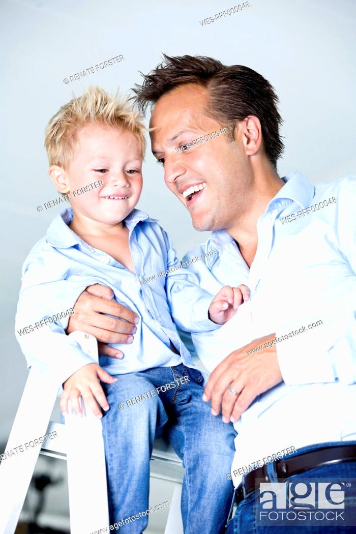 Stock Photo: Germany, Son sitting on ladder, father standing besides.