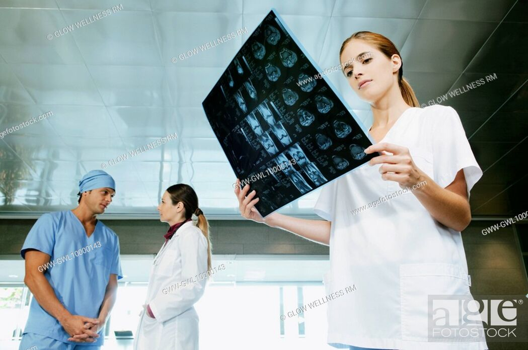 Imagen: Female nurse examining an X-Ray with her colleagues discussing in the background.