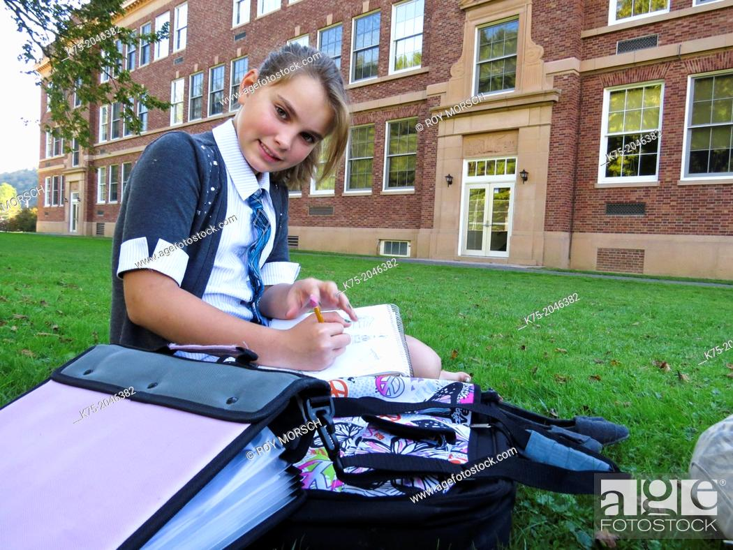 Stock Photo: Girl studying on lawn outside school.