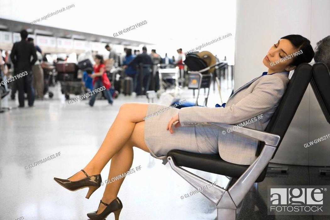 Stock Photo: Side profile of a businesswoman sleeping on a chair at an airport.