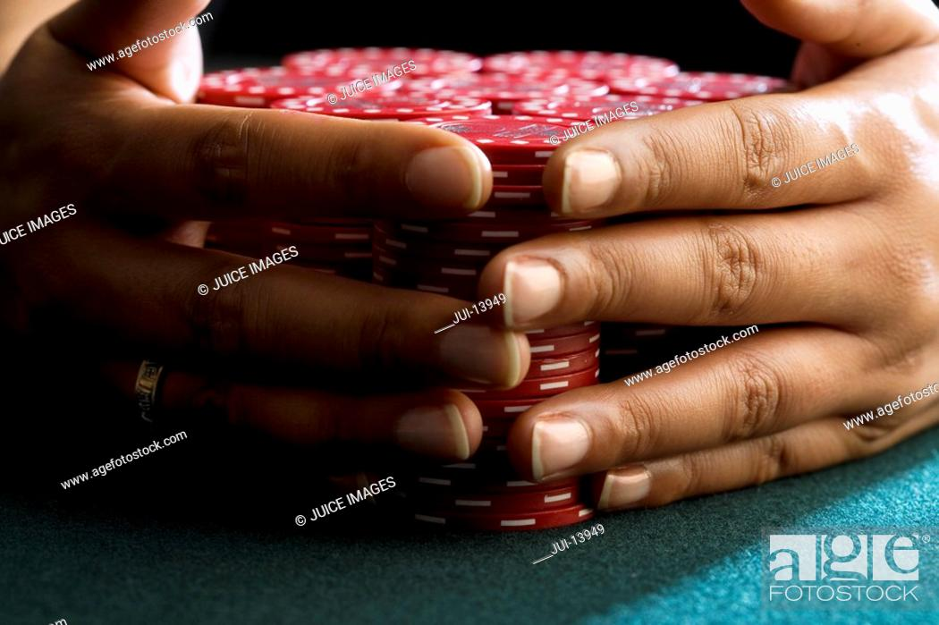 Stock Photo: Woman with hands around piles of gambling chips on table, close-up of hands.