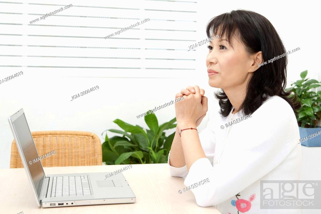 Stock Photo: Woman holding hands and looking away.