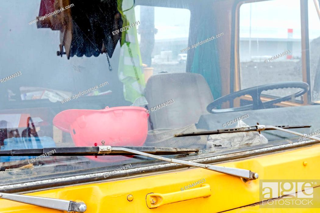 Stock Photo: Front view cabin of the yellow mobile crane with winch in reflection on windscreen glass.
