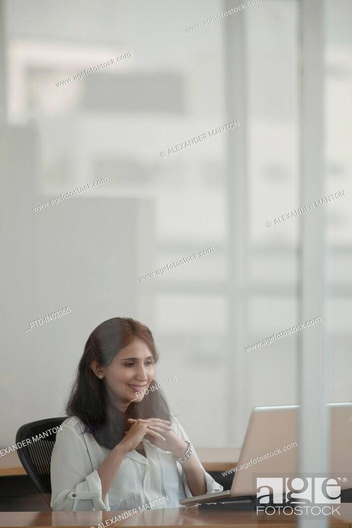 Stock Photo: Singapore, Businesswoman using laptop in office.