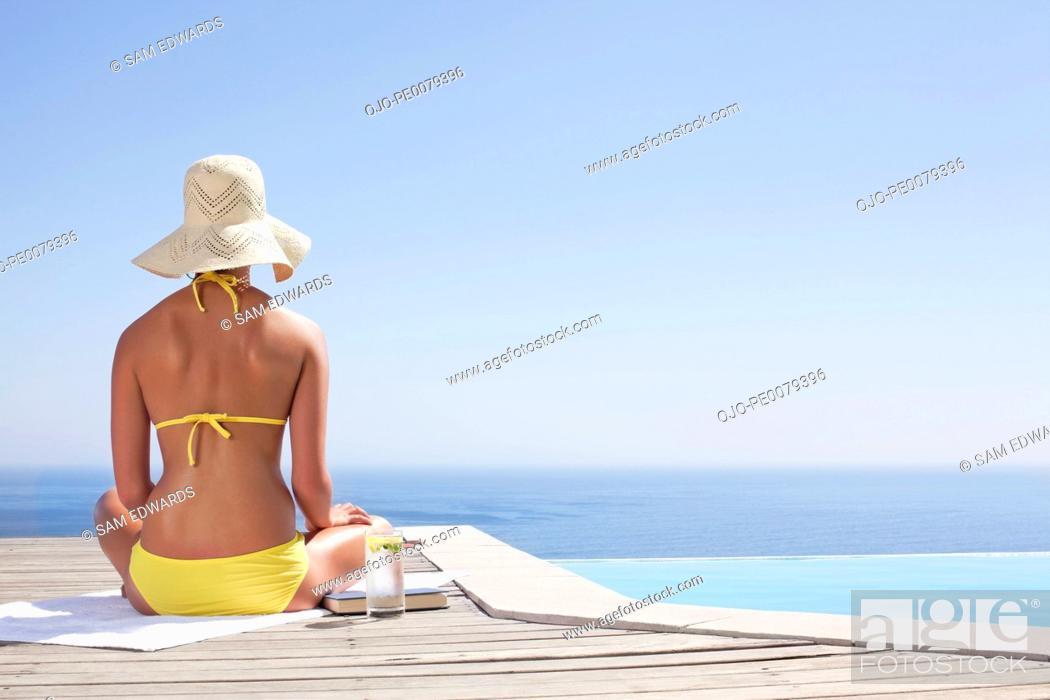 Stock Photo: Woman in bikini sitting near swimming pool.