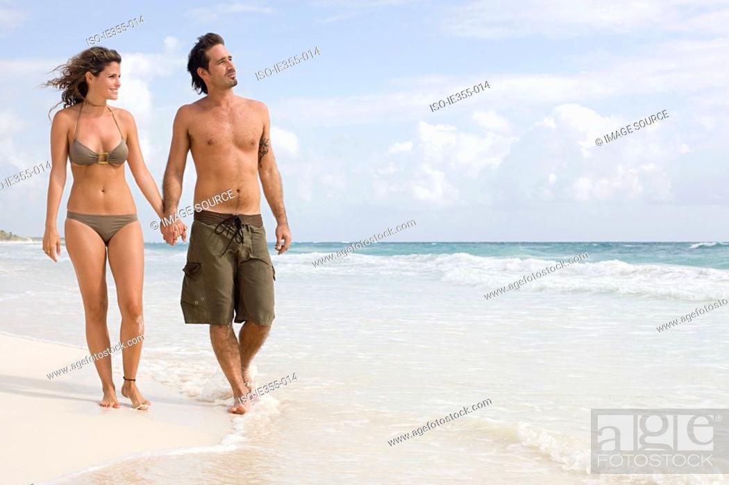 Stock Photo: A couple walking along a beach.