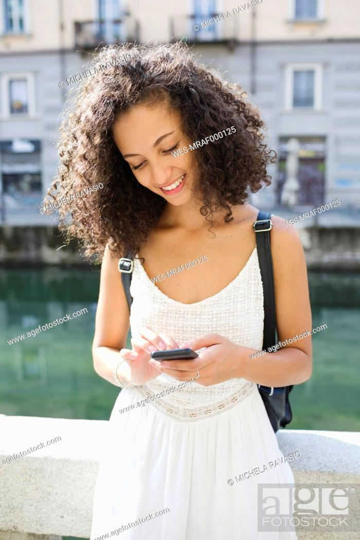 Stock Photo: Portrait of smiling young woman text messaging.