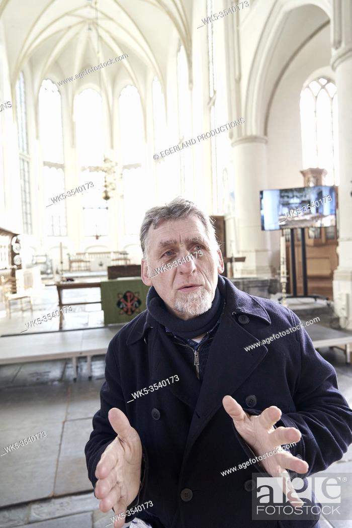 Stock Photo: senior man explaining inside church in Bolsward, Friesland, Netherlands.