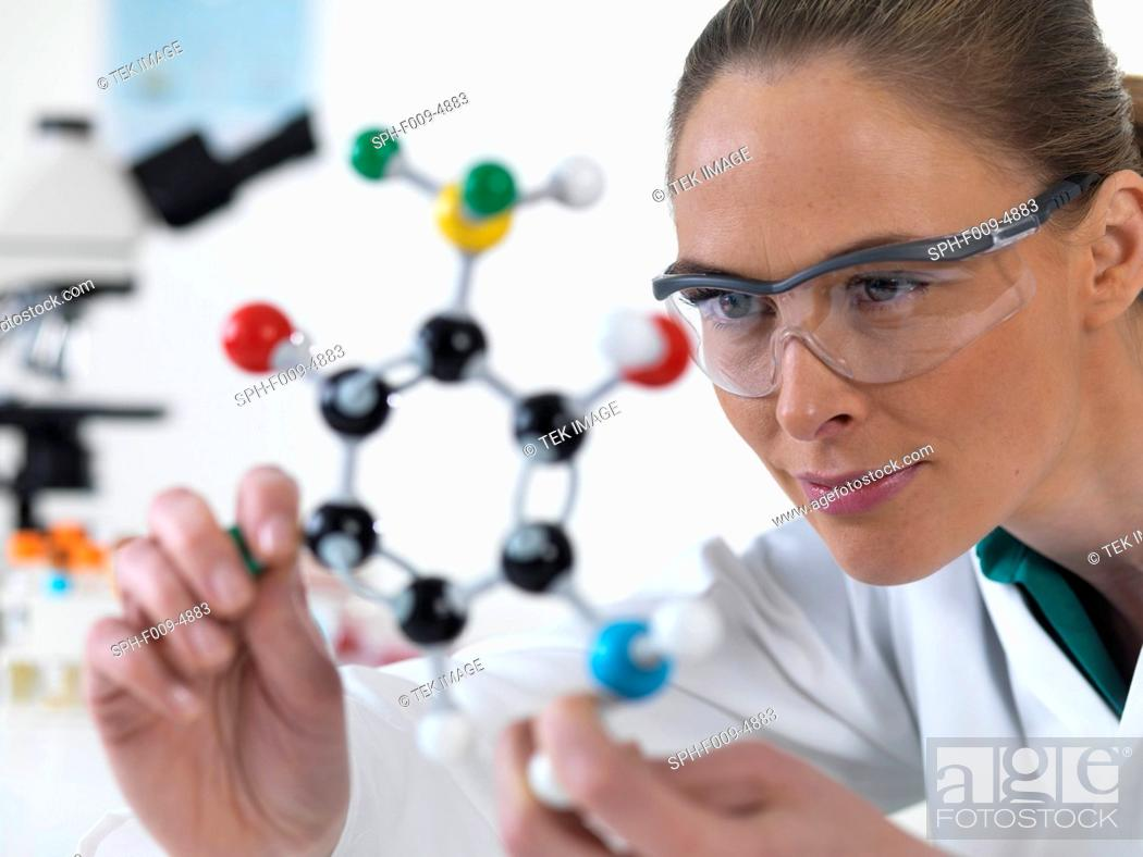 Stock Photo: Female scientist looking at a molecular model.