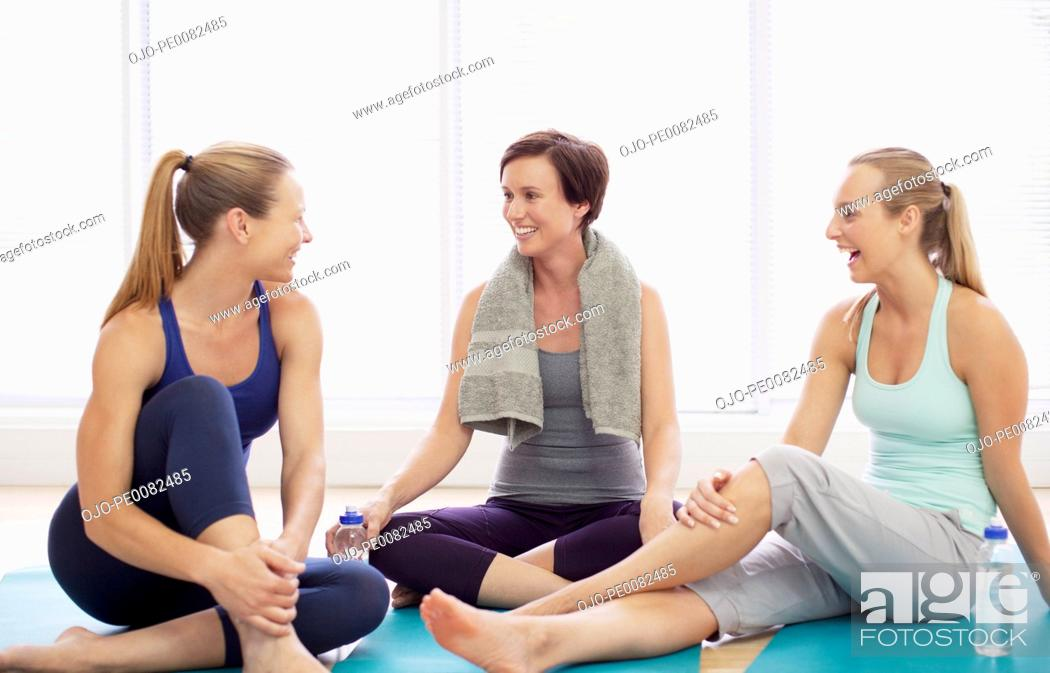 Stock Photo: Smiling women resting on exercise mats.