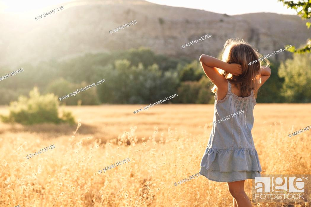 Imagen: Young blonde girl playing with sunlight in the fields sunset wearing a dress with hill in the background.