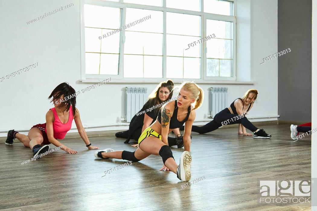 Imagen: Confident young females practicing splits while dancing in studio.