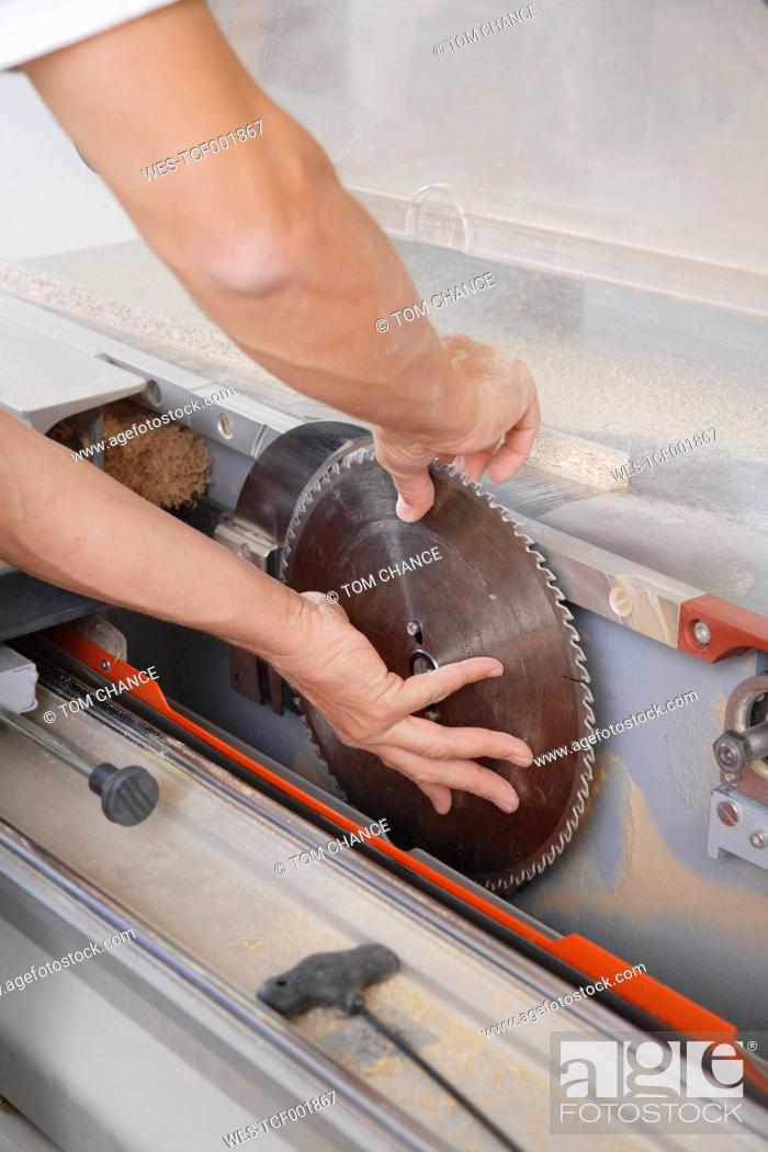 Stock Photo: Germany, Upper Bavaria, Schaeftlarn, Carpenter fixing blade to electrical machine.