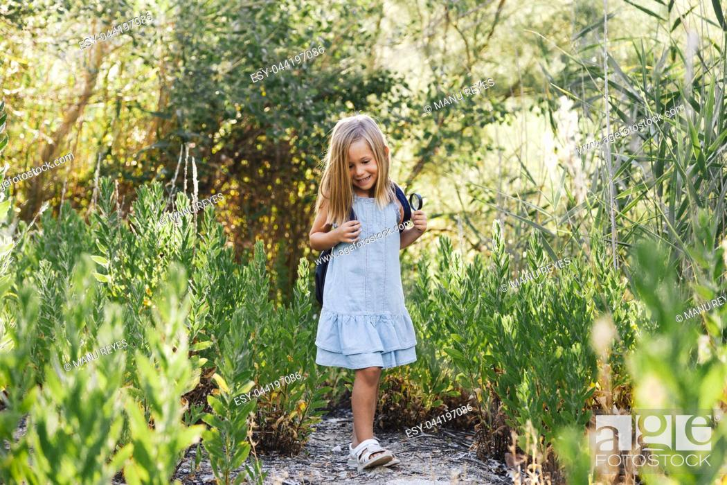 Stock Photo: Young blonde girl walking in the field wearing a dress with a magnifying glass in her hand an backpack.